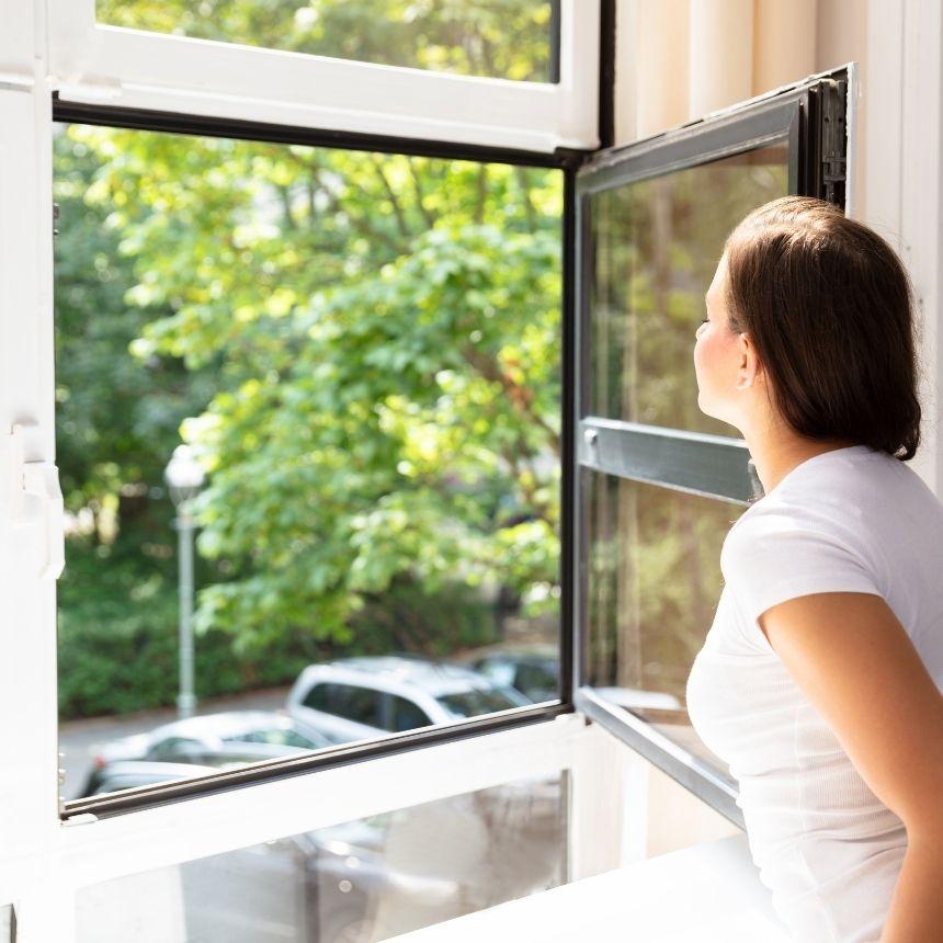 Våra vanligaste frågor och svar, kvinna tittar ut genom nytvättat fönster.
