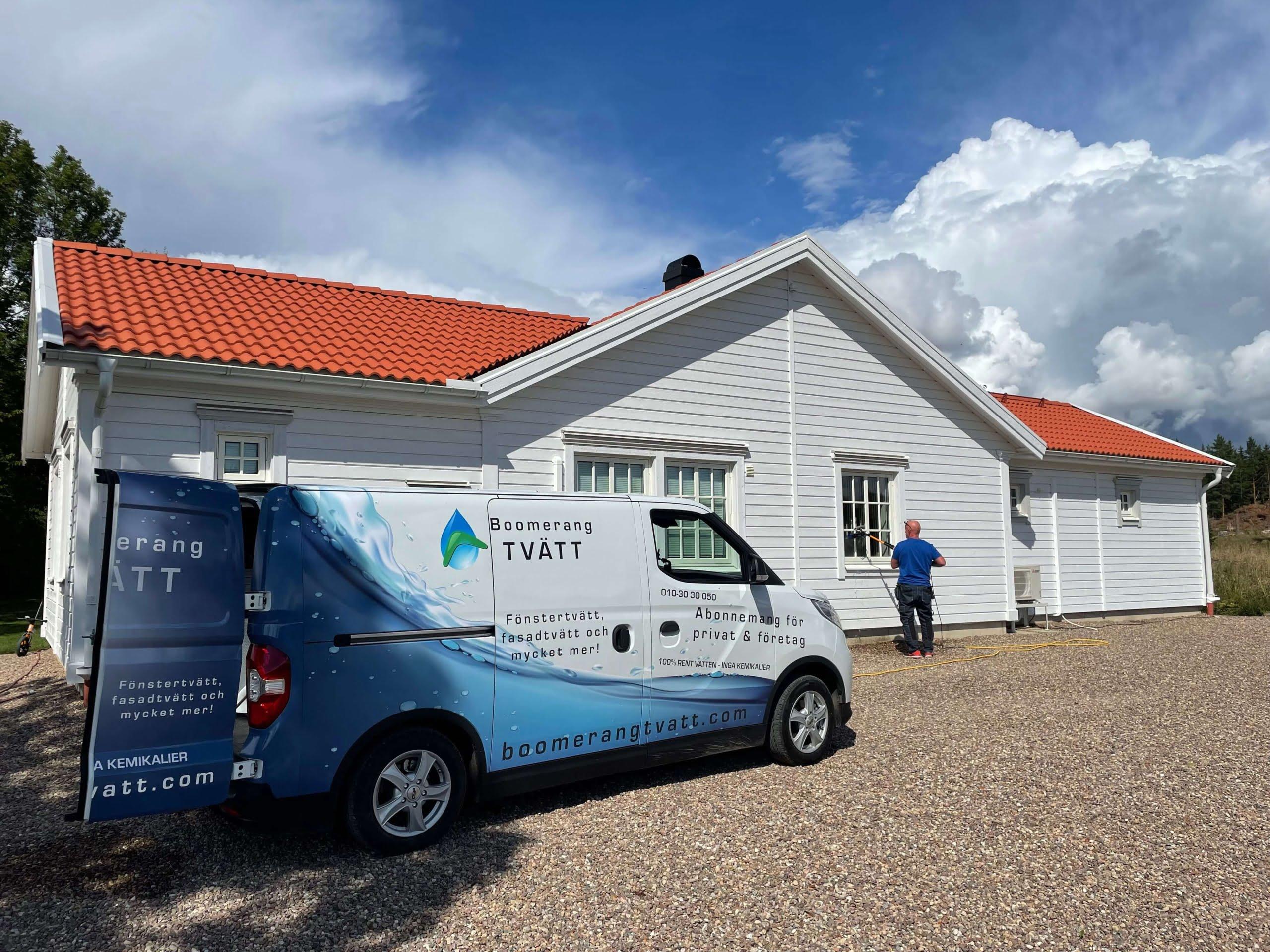 fönstertvätt och företagsbil framför ett vitt vackert hus